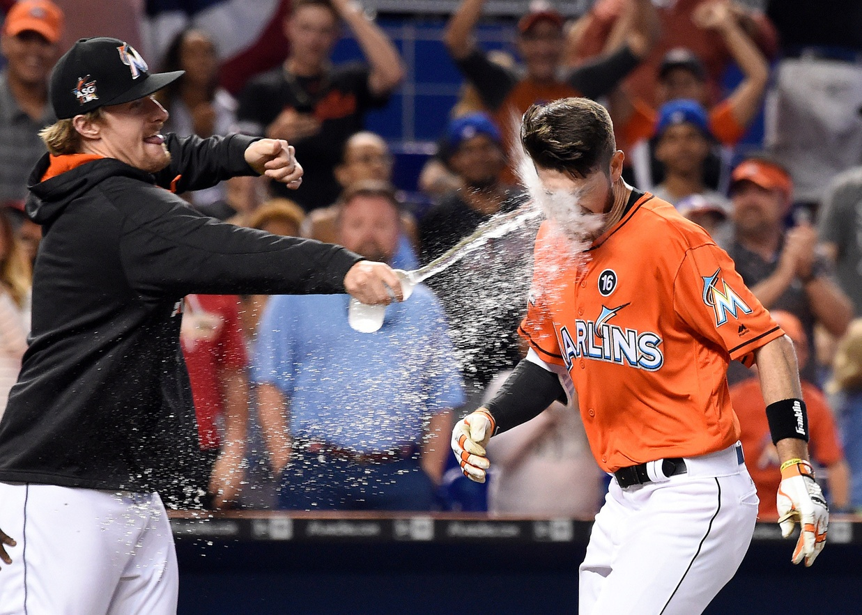 Apr 16, 2017; Miami, FL, USA; Miami Marlins Miami Marlins pinch hitter JT Riddle (R) is splashed with water by Marlins starting pitcher Tom Koehler (L) after hitting the game winning two run homer during the ninth inning against the New York Mets at Marlins Park. Mandatory Credit: Steve Mitchell-USA TODAY Sports